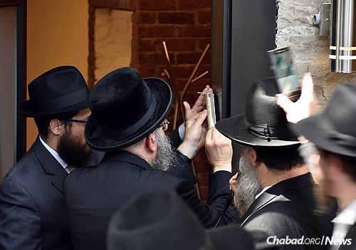 Affixing the mezuzah (Photo: Benjamin Zarka)