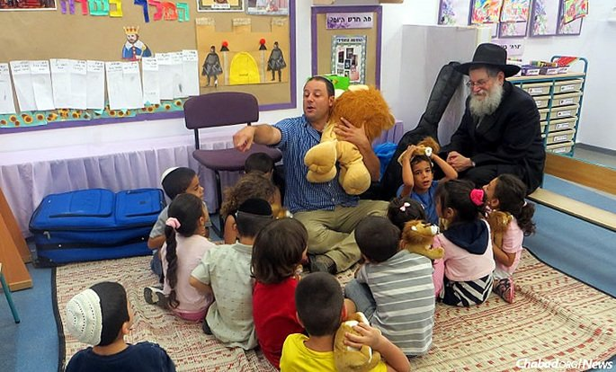 """Rabbi Mendel Lieberman, right, founder of Chabad's """"Chai Ashkelon"""" program, with some of the 1,200 hospitalized children in Israel who will get to participate in summer camp this year, the program's 35th year running."""