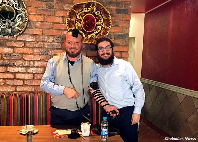 Michael, left, wraps tefillin for the first time, assisted by Rabbi Zalman Goldberg. The South African recently learned that he was Jewish.