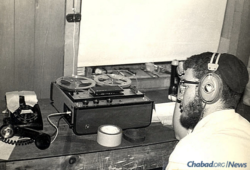 """In January 1970, for the very first time, the Rebbe's talk at the farbrengen after Shabbat was broadcast live through a phone-line hook-up to 1,000 Chassidim gathered in the village of Kfar Chabad, Israel. Inside the """"World Lubavitch Communications Center"""" (WLCC), Meni Wolff can be seen working on the broadcast. (Photo: Mulik Rivkin Archive)"""