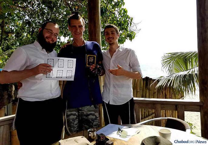Shmuel Butler, left, and Ari Herson, right, with a friend in Negril, displaying some of their freshly printed Tanyas.