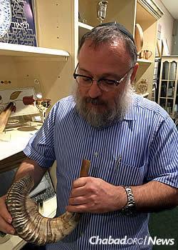 Yossi Gurevitch examines a shofar in his Judaica shop on Long Island, N.Y.