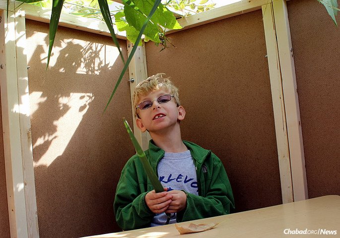 Evan Lovy holds a lulav (palm frond) at Sukkot time. He is part of the Efshar Circle, a program that provides a Jewish and Judaic program developed especially for students with a variety of special needs.