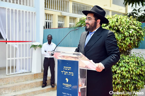 Rabbi Levi Yitzchak Chekly, co-director of Chabad of Angola with his wife, Devorah Leah, welcomes the crowd at the grand opening of the new building and synagogue. (Photo: Israel Bardugo)