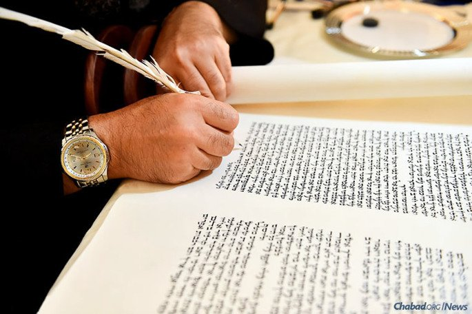 Rabbi Dovid Cohen of Montreal, Canada, puts the finishing touches on a Torah scroll for the Angolan Jewish community. A Hachnasat Sefer Torah celebration, or welcoming of a Torah scroll to its new home, was followed by dinner and live music. (Photo: Israel Bardugo)