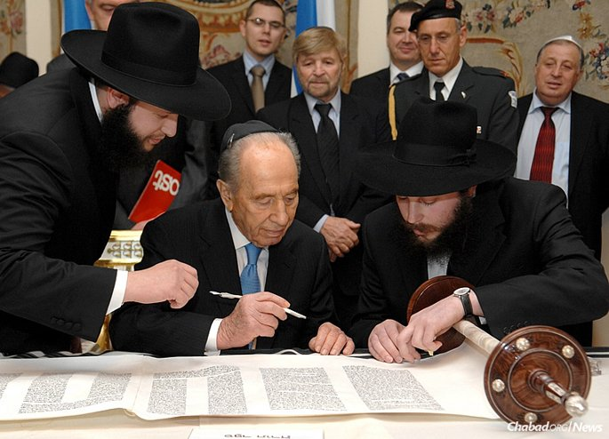 Shimon Peres, who served in a variety of political and defense positions before and after Israel's founding, and who later in life became the nation's ninth president and the world's oldest head of state, passed away in Tel Aviv at the age of 93. Here Peres writes a letter in a new Torah in Belweder, Poland, accompanied by Rabbi Shalom DovBer Stambler, left, director of Chabad Lubavitch of Poland, and Rabbi Levi Stambler, director of the Jewish Community of Dneprodzerzhinsk, Ukraine.
