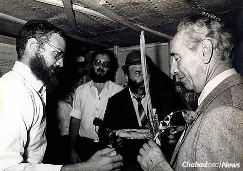 Peres shakes the lulav with Rabbi Schneur Goodman of Ashdod, Israel, circa 1979.