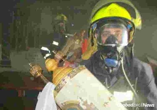 Firefighters rescue a Torah scroll.