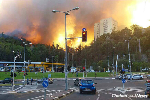 Flames overwhelm Haifa, shown here as they surround an apartment building.
