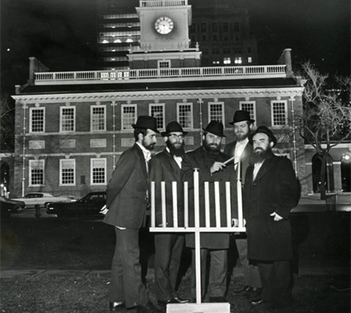 Chabad representative Rabbi Abraham Shemtov (right) and other rabbis light the first public menorah in front of Philadelphia's iconic Liberty Bell.