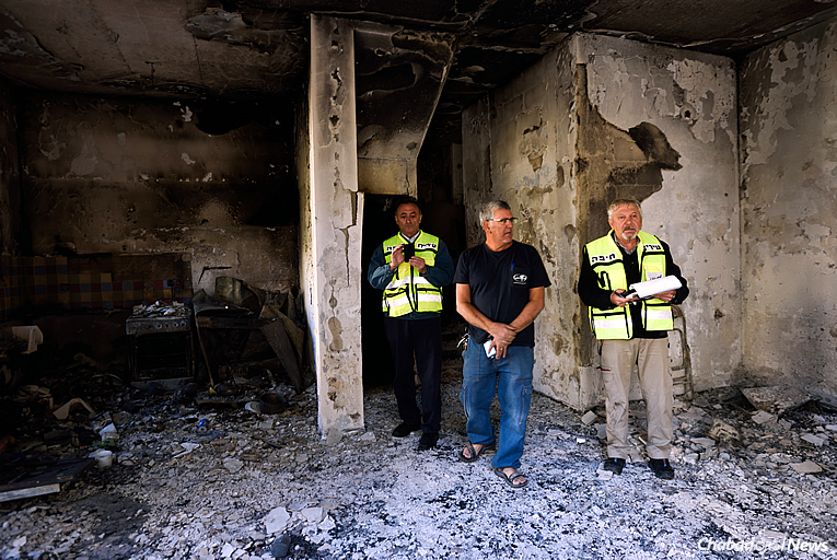 """Israelis inspect the damage to a burnt house hit by fire in the northern city of Haifa. Chabad on Campus International has established the """"Israel Under Fire Relief Fund"""" to assist those affected by the massive fires, which have now been contained. (Photo: Gili Yaari/Flash90)"""