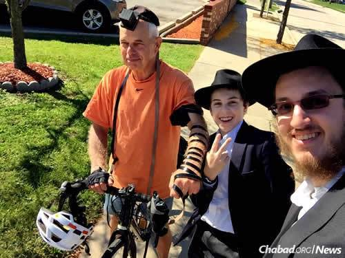 Mendel Greenberg helps a biker with tefillin, while Rabbi Ezra Wiemer, right, looks on.