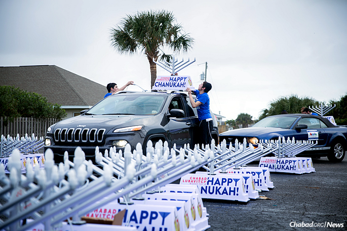 It's almost time for Chanukah car-menorah parades, which will take place during the eight-day Festival of Lights. Here, attaching them all last year in Satellite Beach, Fla. (Photo: Chavi Konikov)