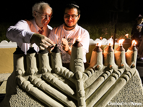 Community member Leslie Evans, left, lit the sand menorah in Palm Beach.