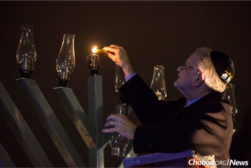 Former Gallaudet President Dr. T. Alan Hurwitz lights the shamash candle at the first public menorah-lighting ceremony (2013) at Gallaudet University in Washington, D.C. (Photo: Emily Cohen)