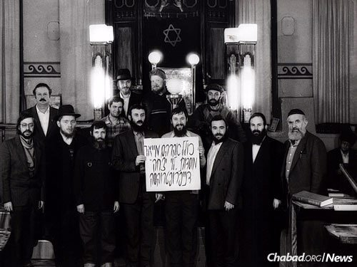 """Members of the """"Kollel Avraham Mayor"""" pose in front of the ark in the old synagogue in Dnepropetrovsk in the early 1990s."""