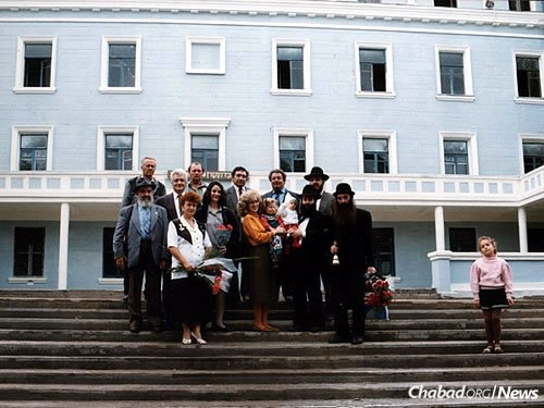 The Kaminezkis with guests outside the massive Levi Yitzchak Schneerson Educational Campus in the early 1990s. The campus sits down the block from the city's former KGB headquarters, where Rabbi Levi Yitzchak Schneerson was held following his 1939 arrest.