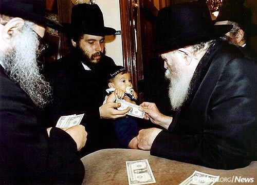 Moskovitz, with his oldest son, Mendel, receives a dollar and a blessing from the Rebbe.