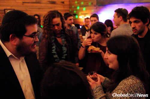 Rabbi Sholom Brook, left, mingles with attendees at the group's recent Chanukah party, the largest event to date.