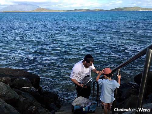 The rabbi and his older son immerse cookware in the water.